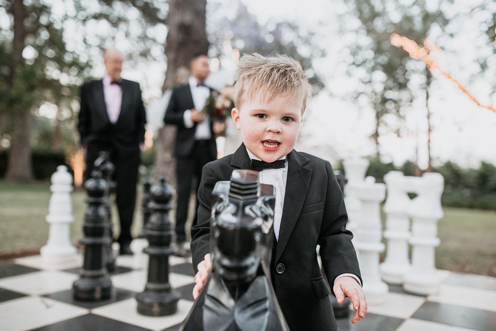 Child dressed in suit playing with outdoor chess set