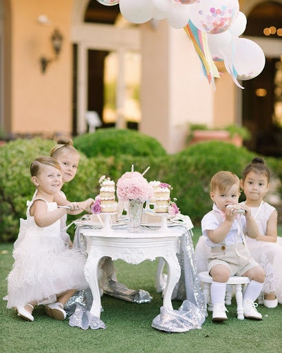 children dressed in white sitting at a kids table at a wedding eating decadent sweets