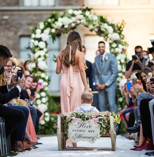 Bridesmaid pulling page boy along in a cart down the aisle