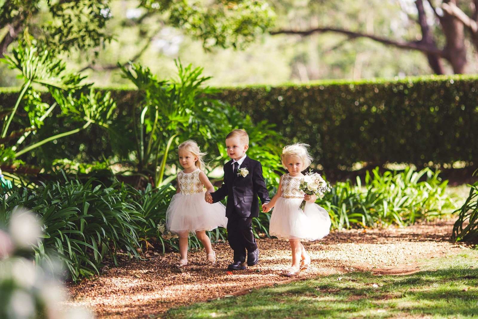 2 flower girls and a page boy walking down a garden path holding hands