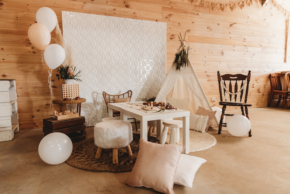 Playroom with teepee, white table and chairs and assorted cushions and treats