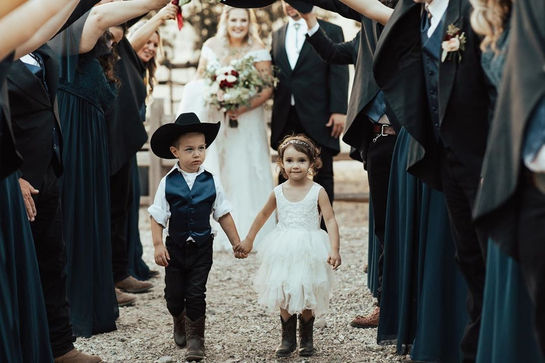 Little cowboy and cowgirl holding hands leading a bride down the aisle