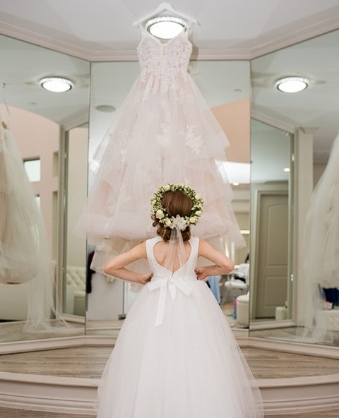Flowergirl standing in a room with mirrors looking up at brides gown