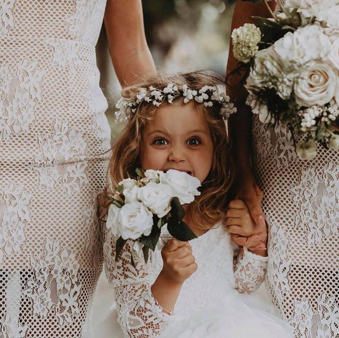 Flowergirl standing between bridesmaids holding a bouquet