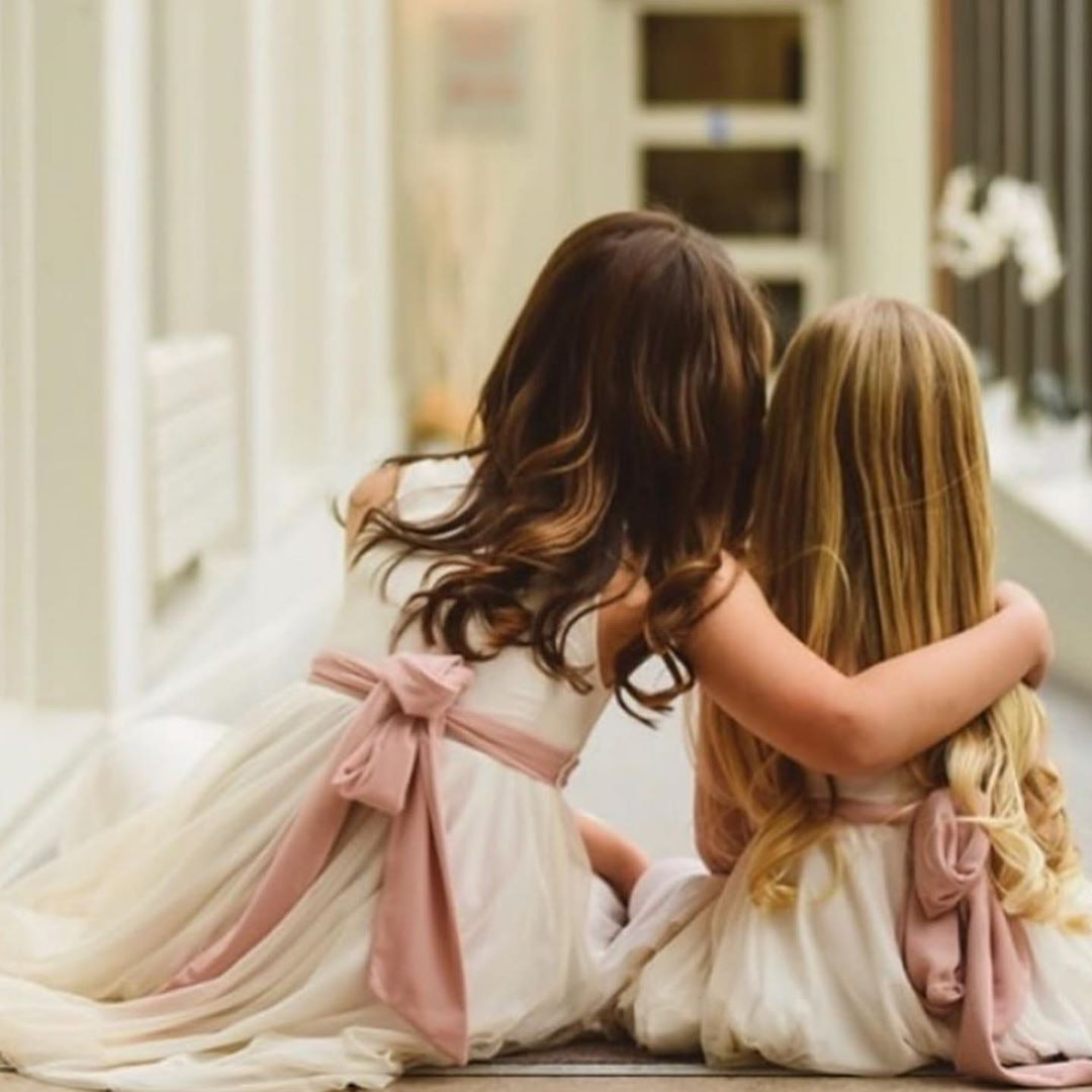 Two flowergirls with their backs to us hugging