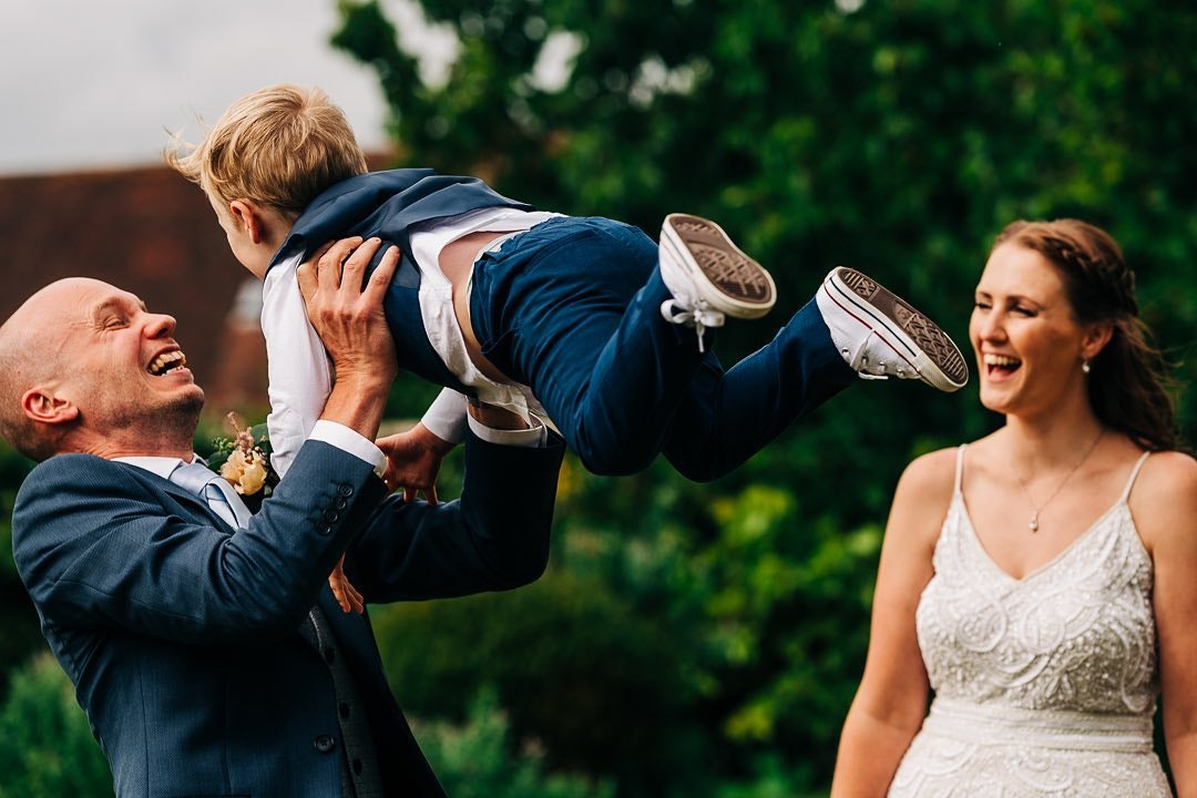 Groom standing next to bride playing with their child by throwing him up into the air
