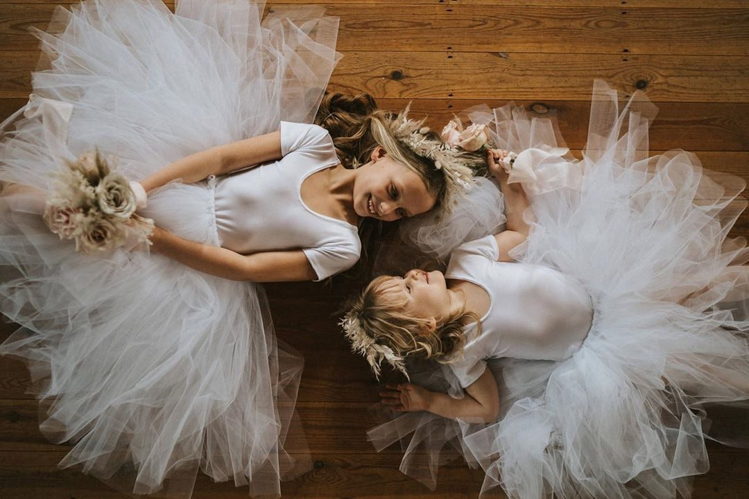 two bridesmaid lying on the floor wearing tutus and holding bouquets
