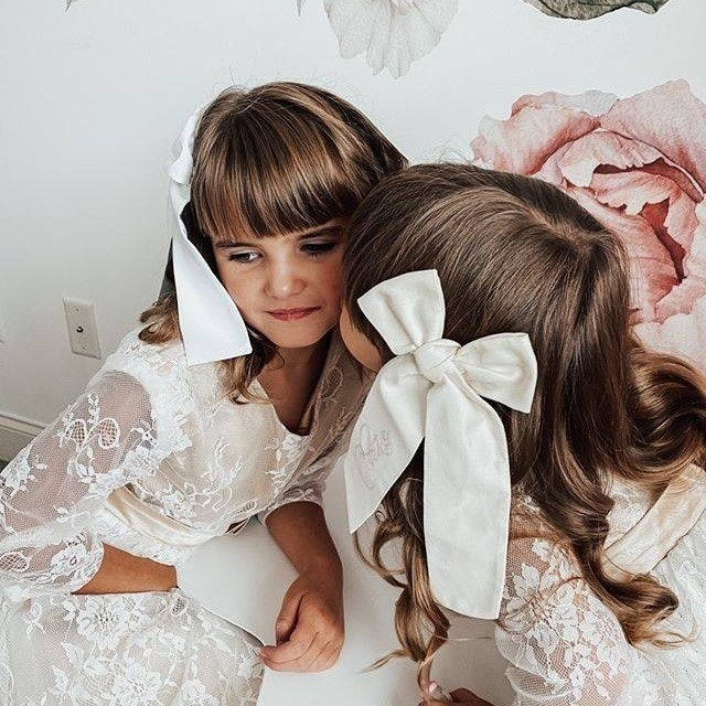 Two flowergirls with bows in their hair talking