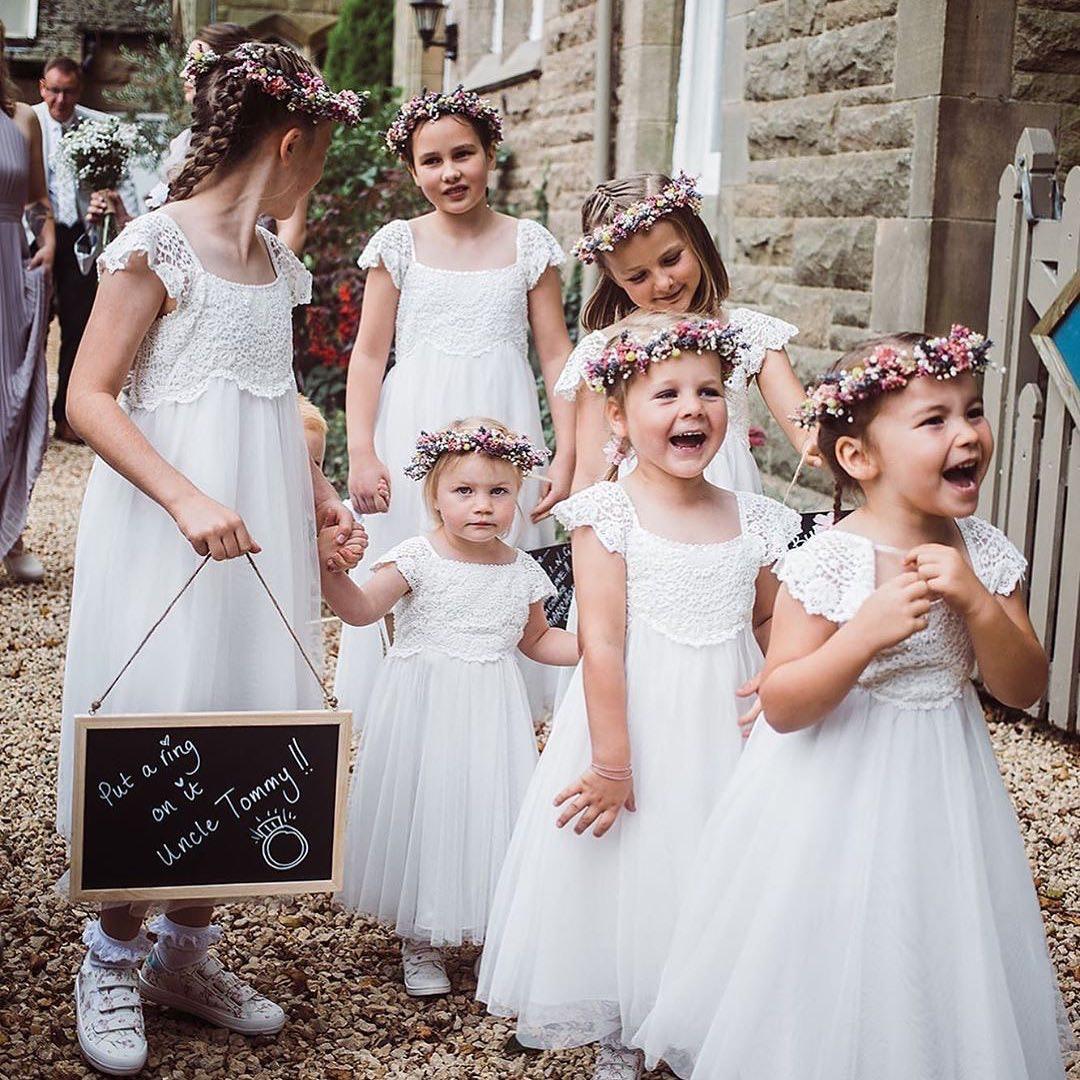 6 flowergirls walking along laughing down the aisle together