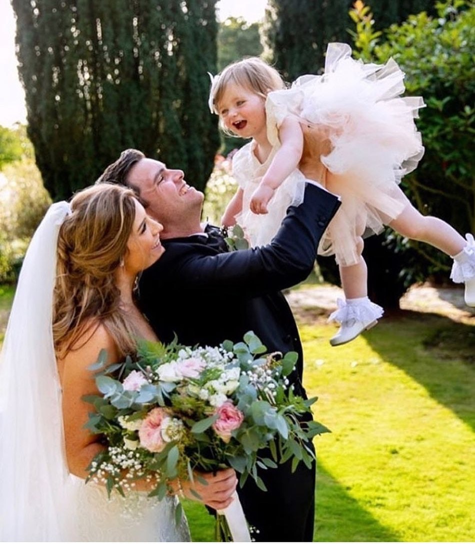 Bride standing next to Groom who is holding up toddler flowergirl