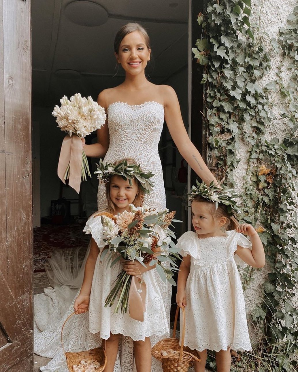 Bride with two flower girls smiling and holding a bouquet