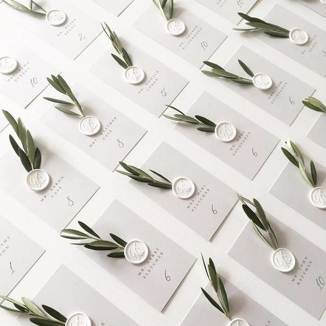 White monogram place cards with olive leaves
