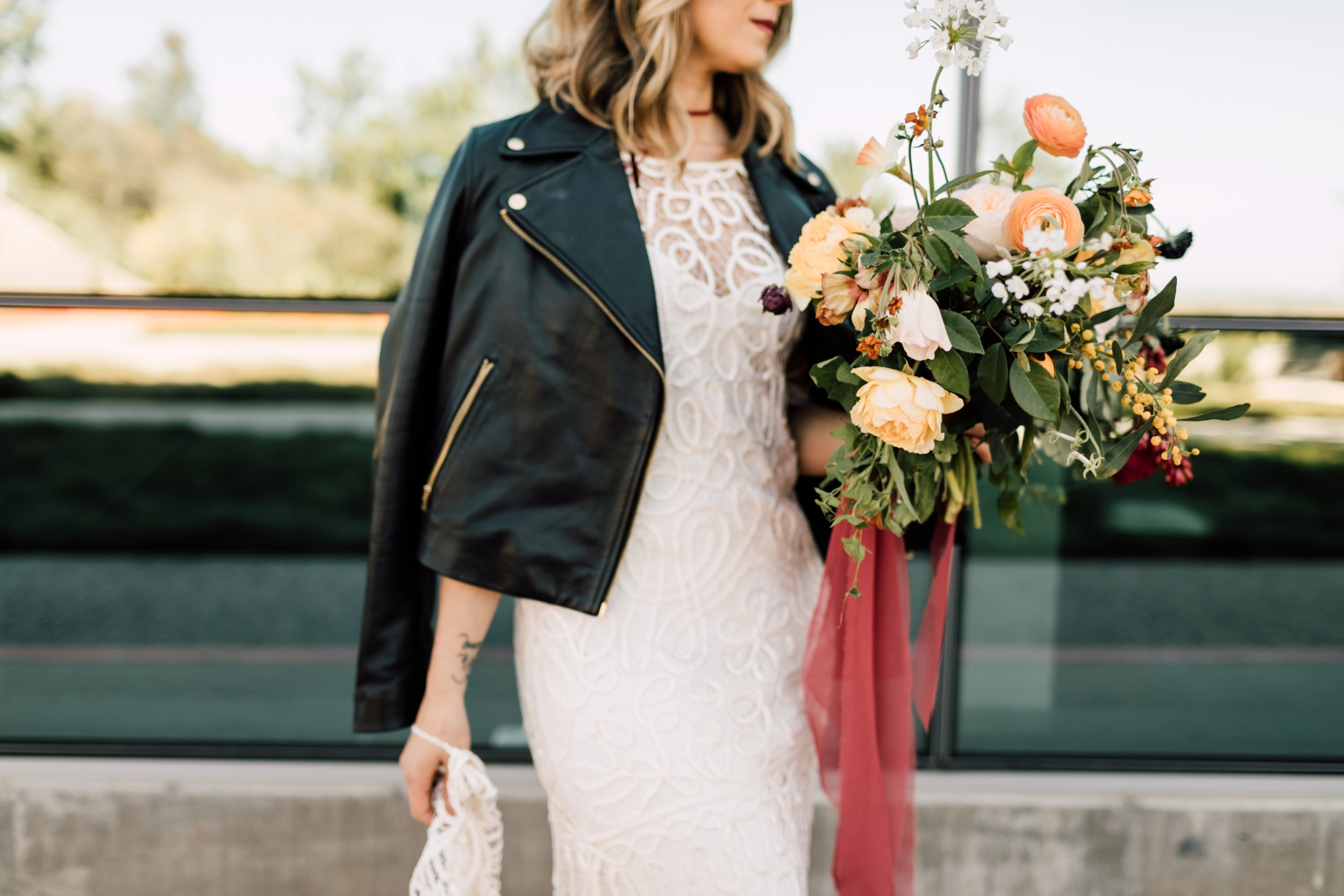 Bride wearing a dress with leather jacket holding a bouquet