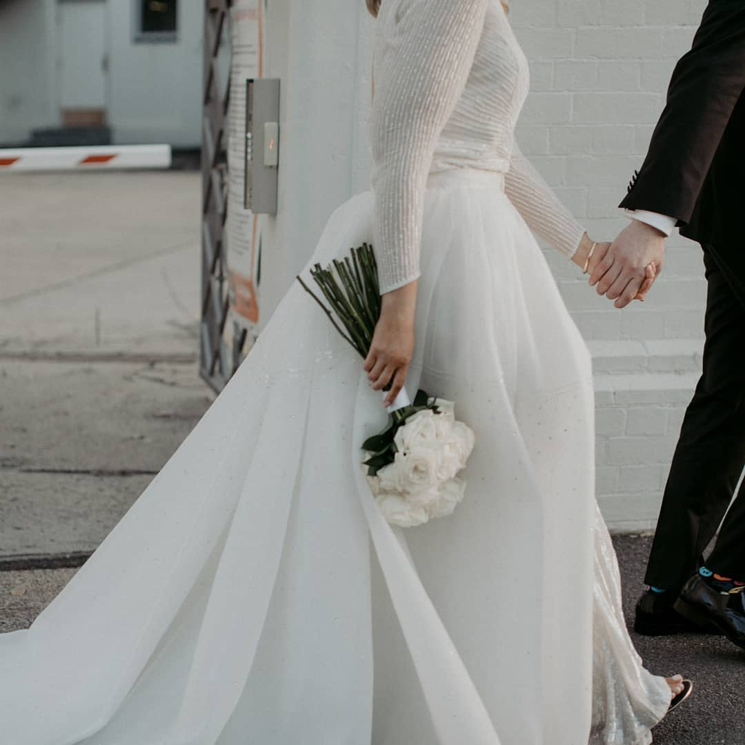 Bride walking along holding grooms hand and holding a bouquet