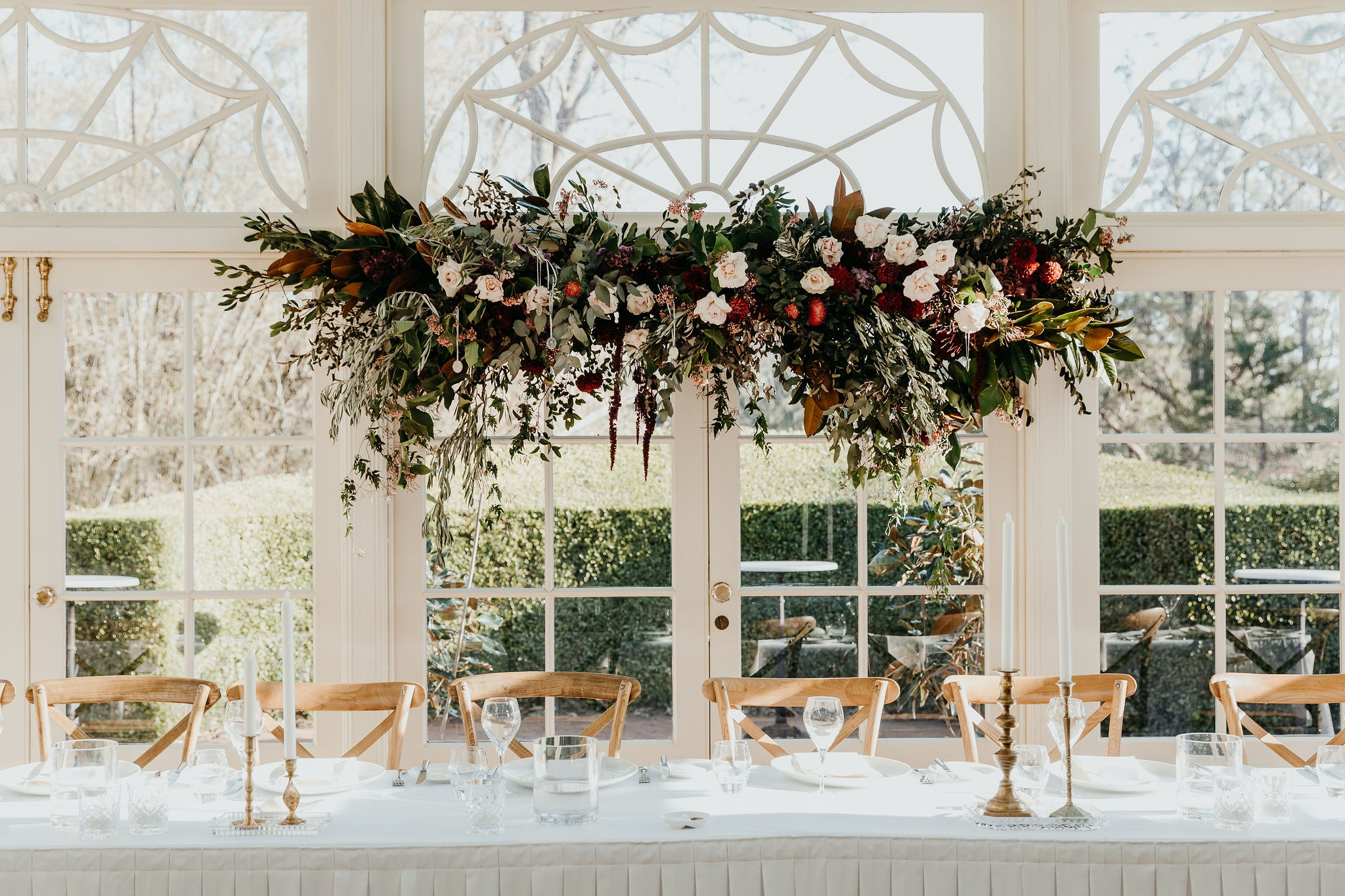 Floral hanging arrangement above table set for wedding guests