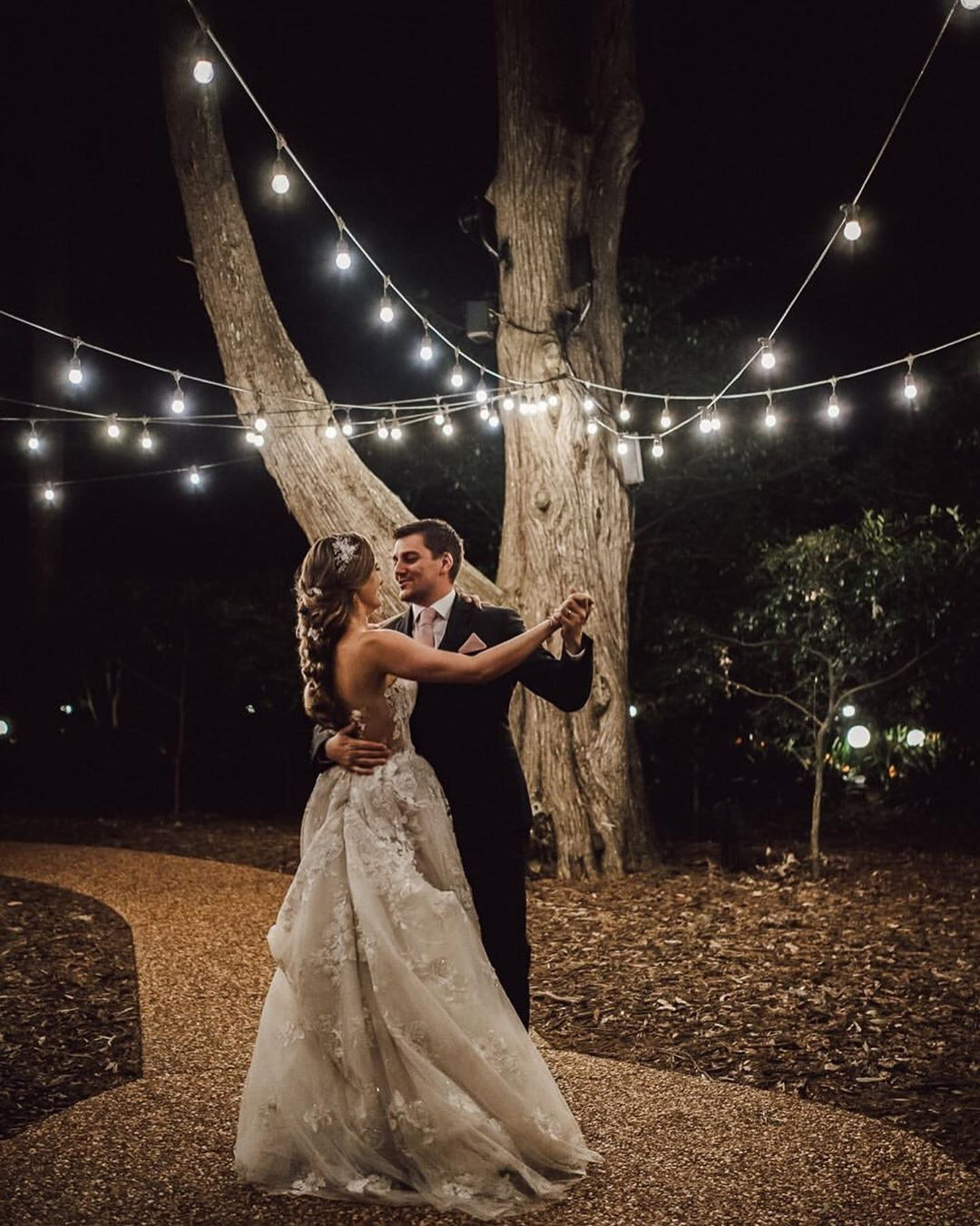 Bride and Groom dancing at night under festoon lights