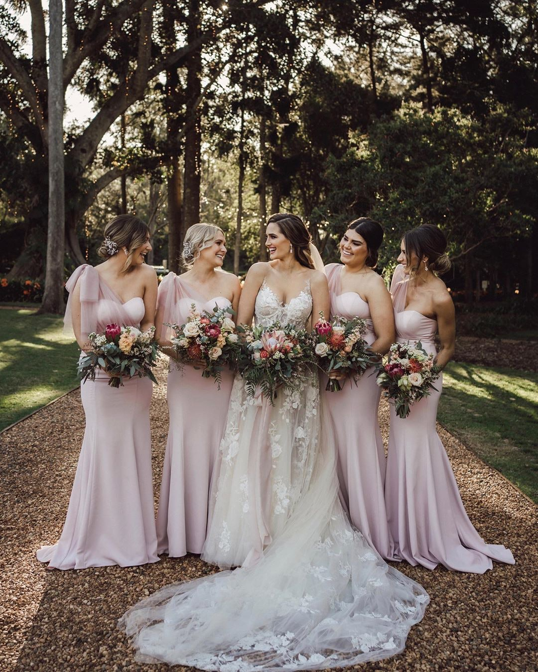 Bride and bridesmaids standing on driveway