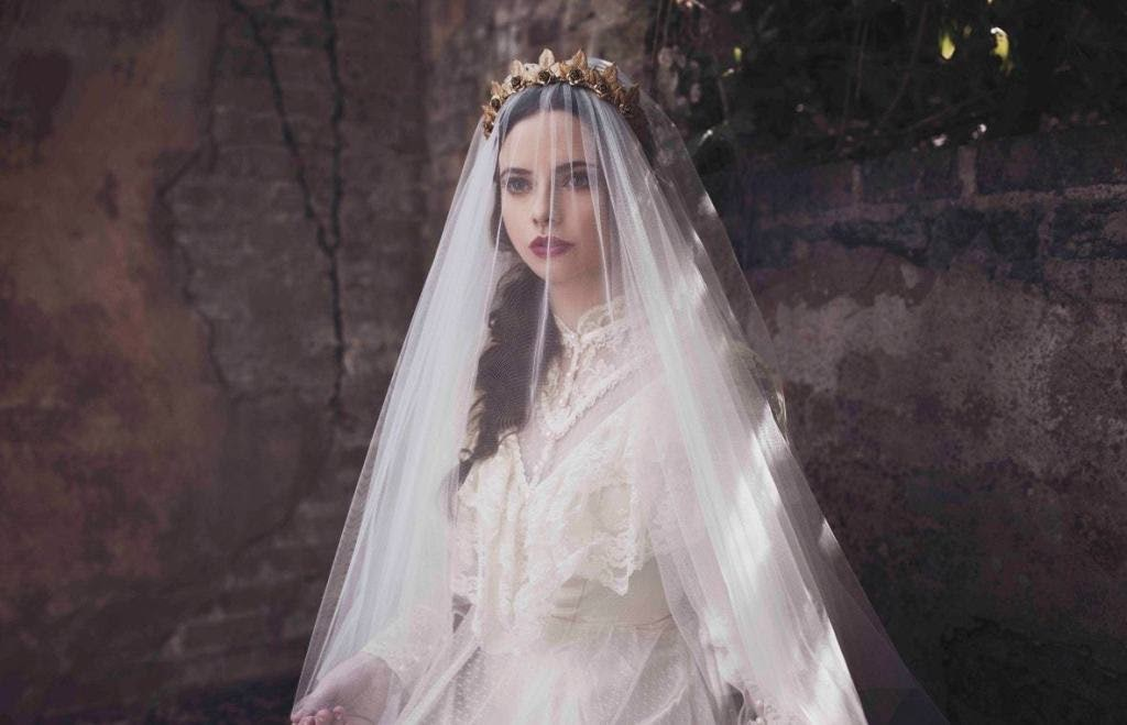 Bride standing in front of a stone wall with a long sheer veil covering her face