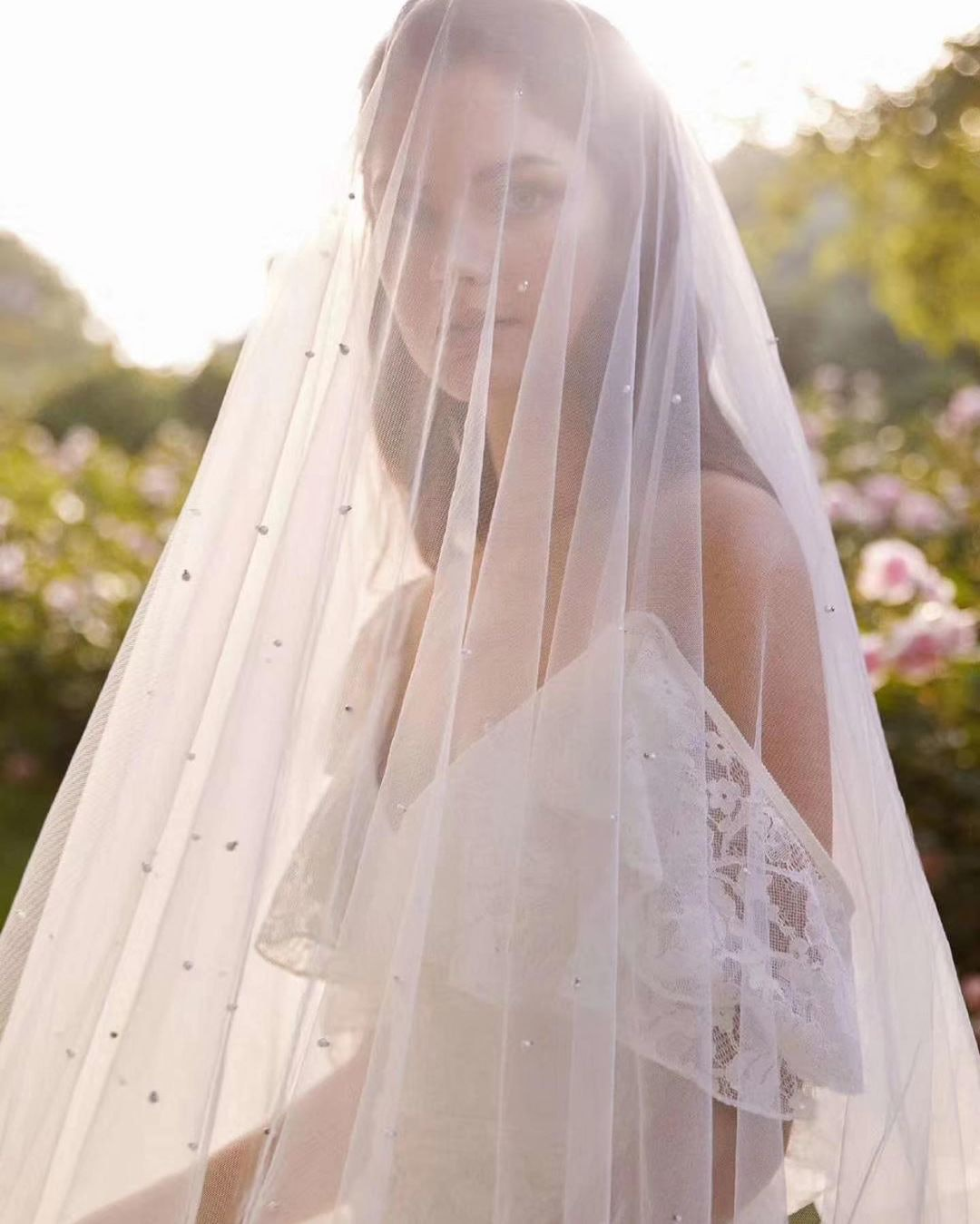 Bride wearing a long veil that covers her face and shoulders