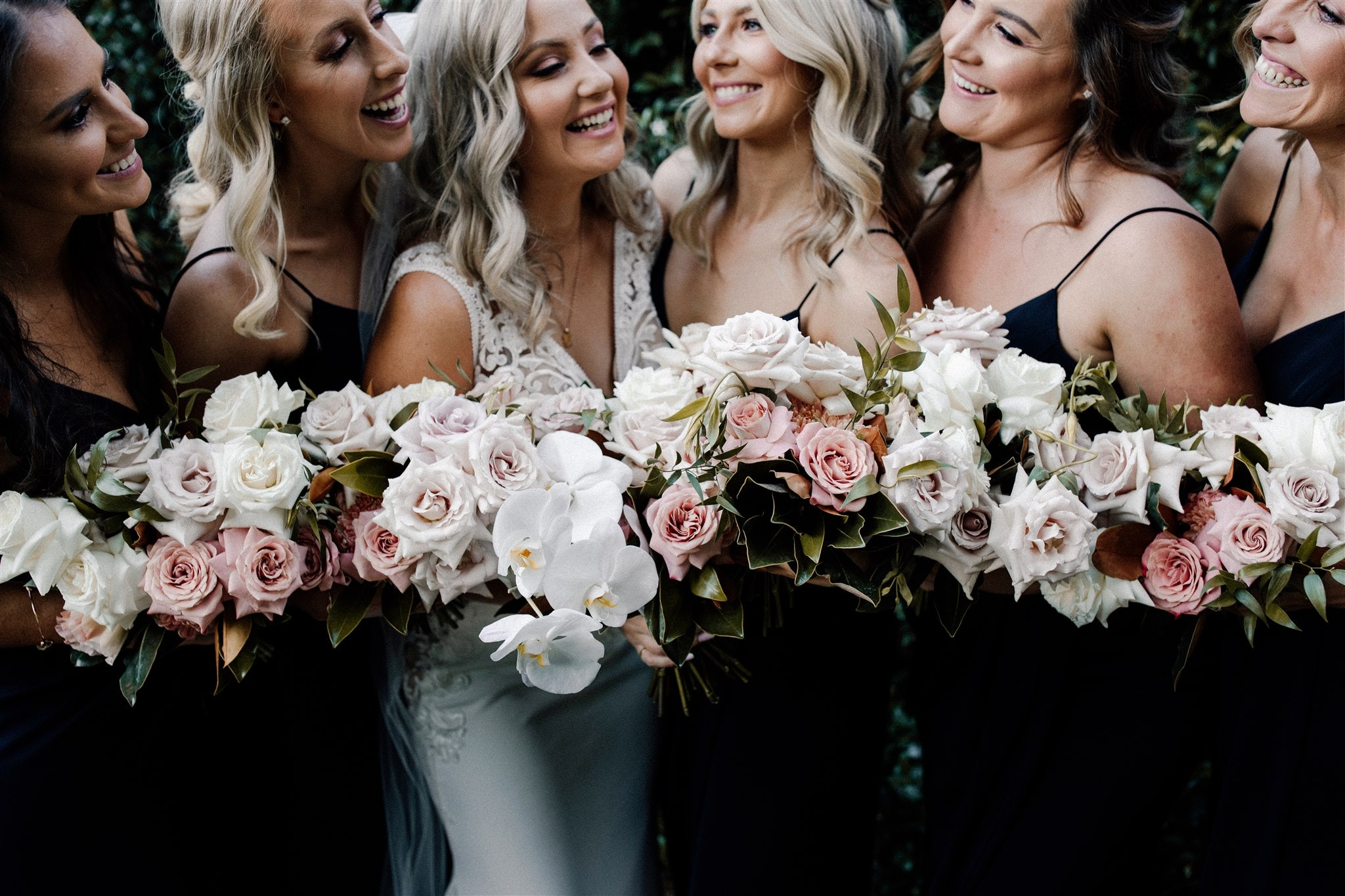 Bride posing with bridesmaids all holding bouquets