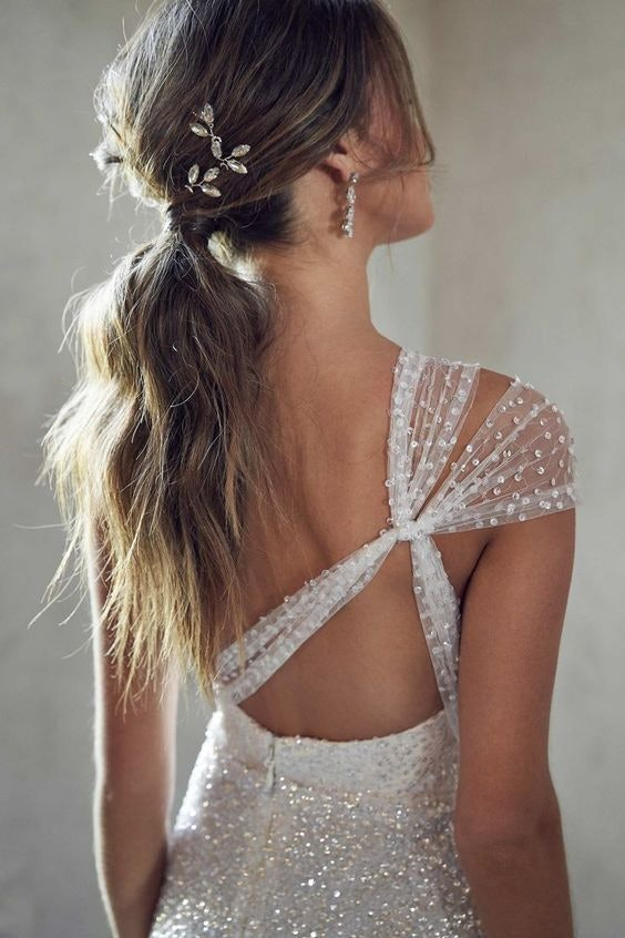 Bride with a low set ponytail with an embellished hair clip