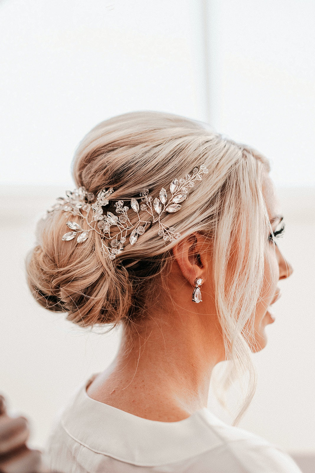 Bride with blonde hair with a low set up do and flowing tendrils