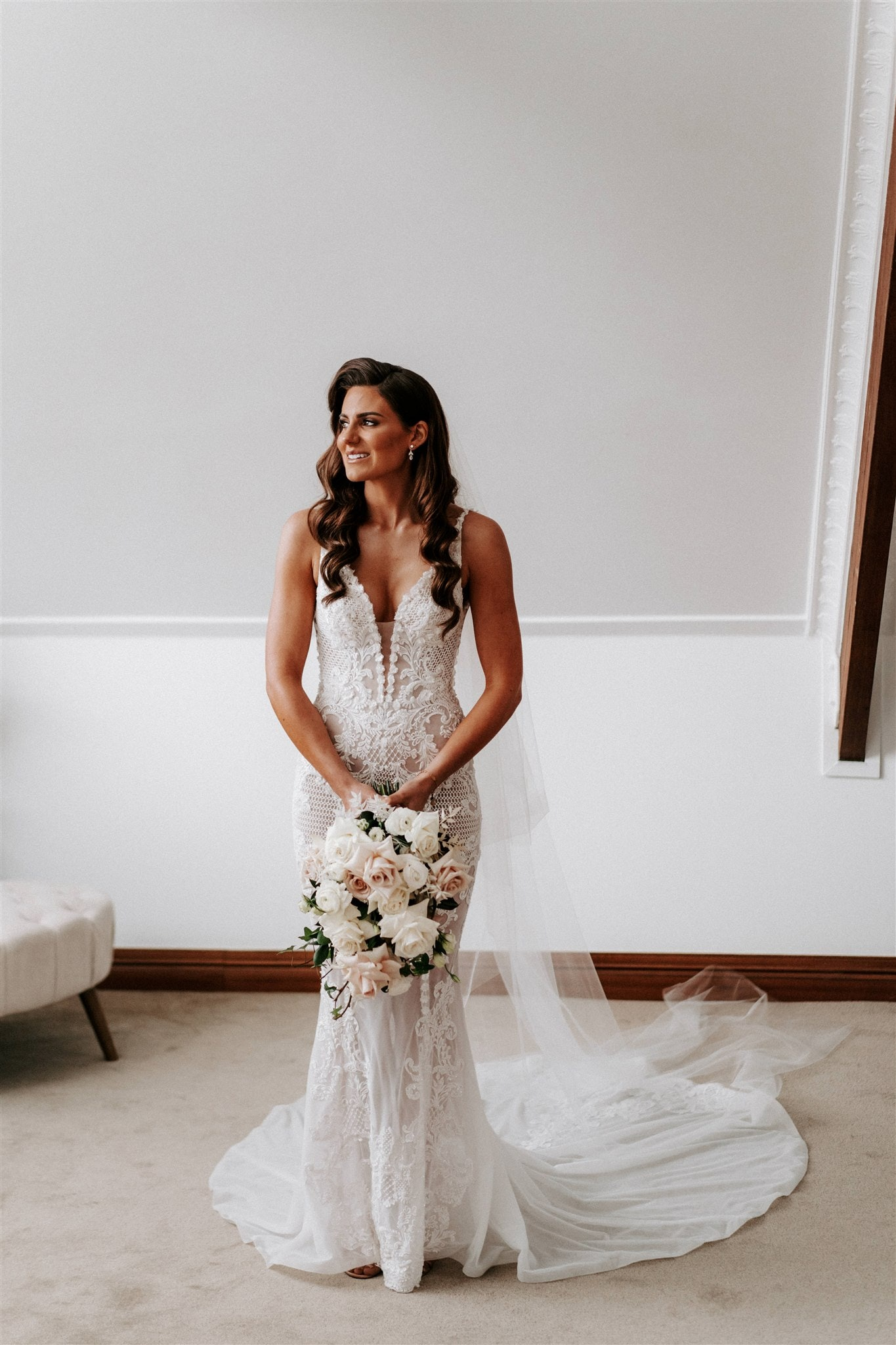 Bride standing alone in a room posing with a bouquet