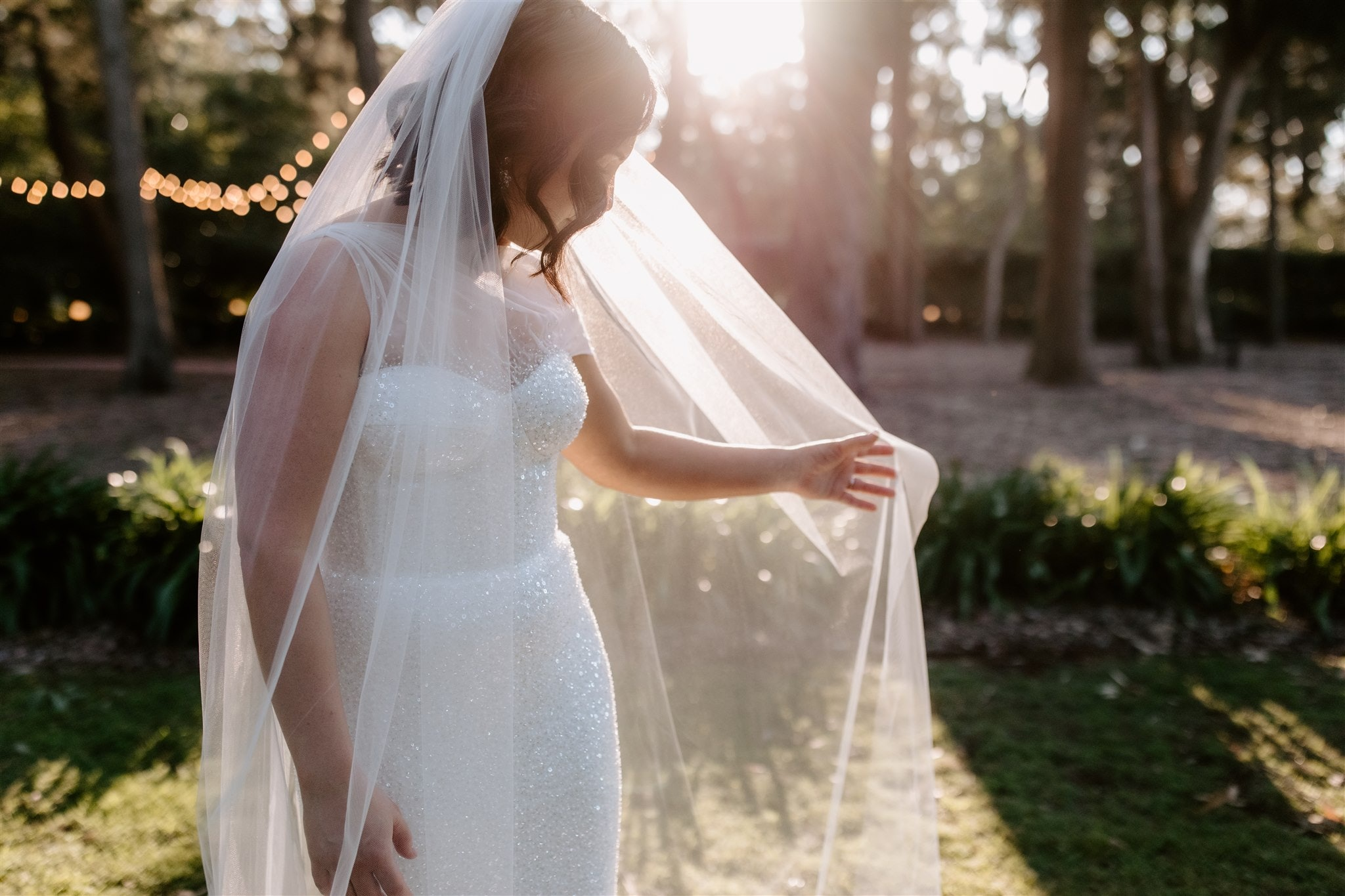 Bride holding out her veil with the sun shining in the background