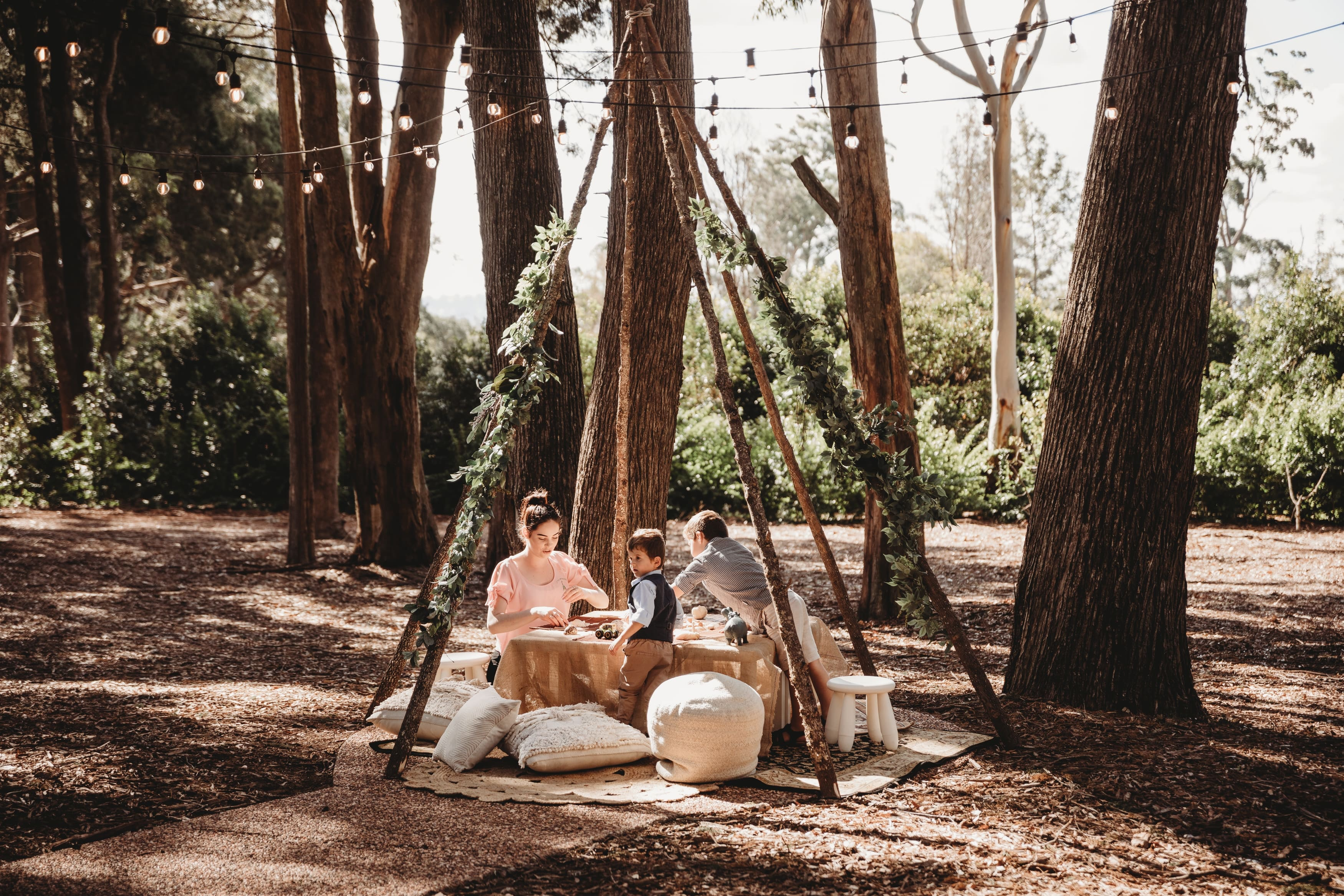 children and woman sitting outside playing under wooden teepee structure