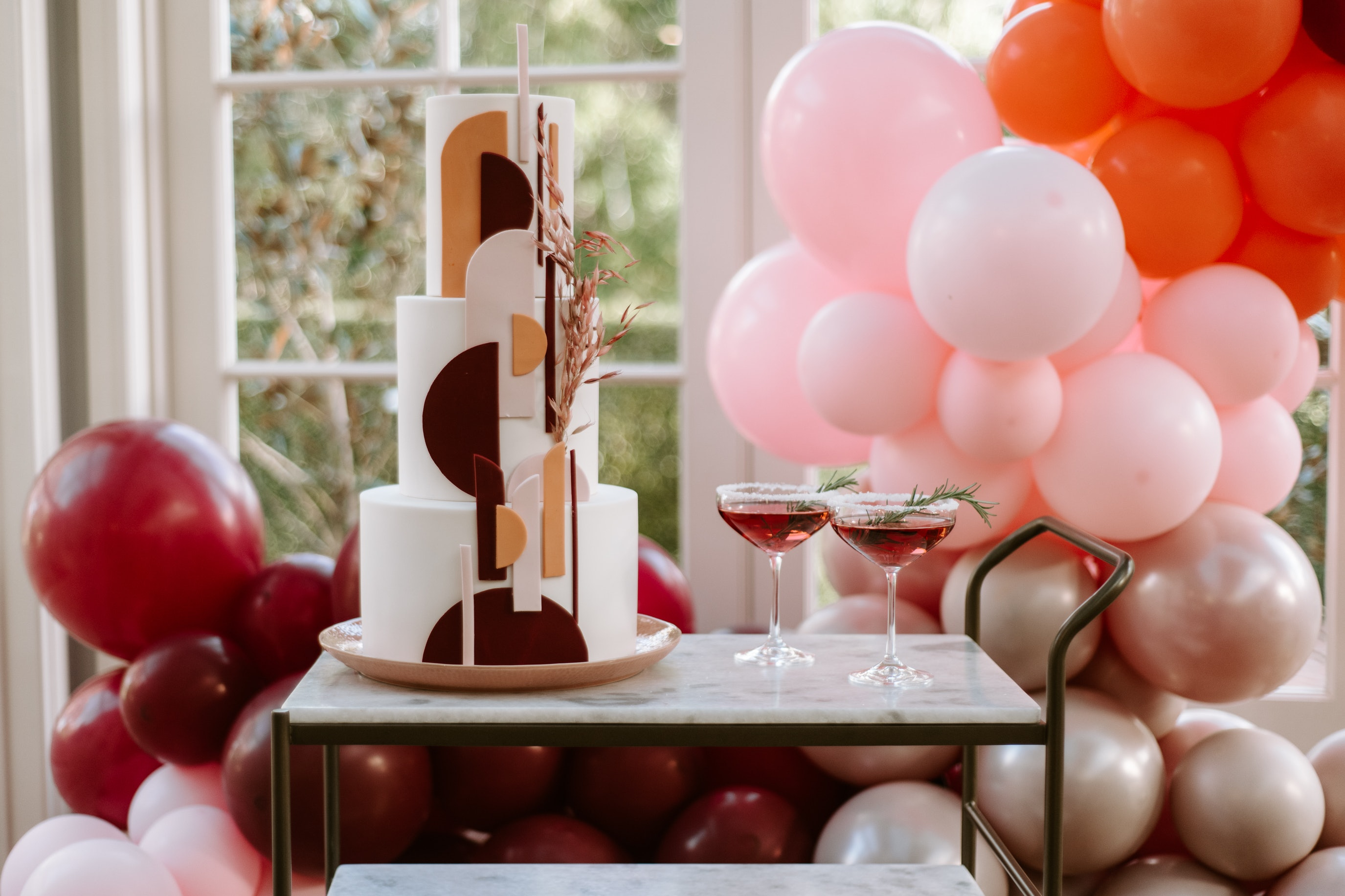 Modern wedding cake on marble cart with balloons in the background
