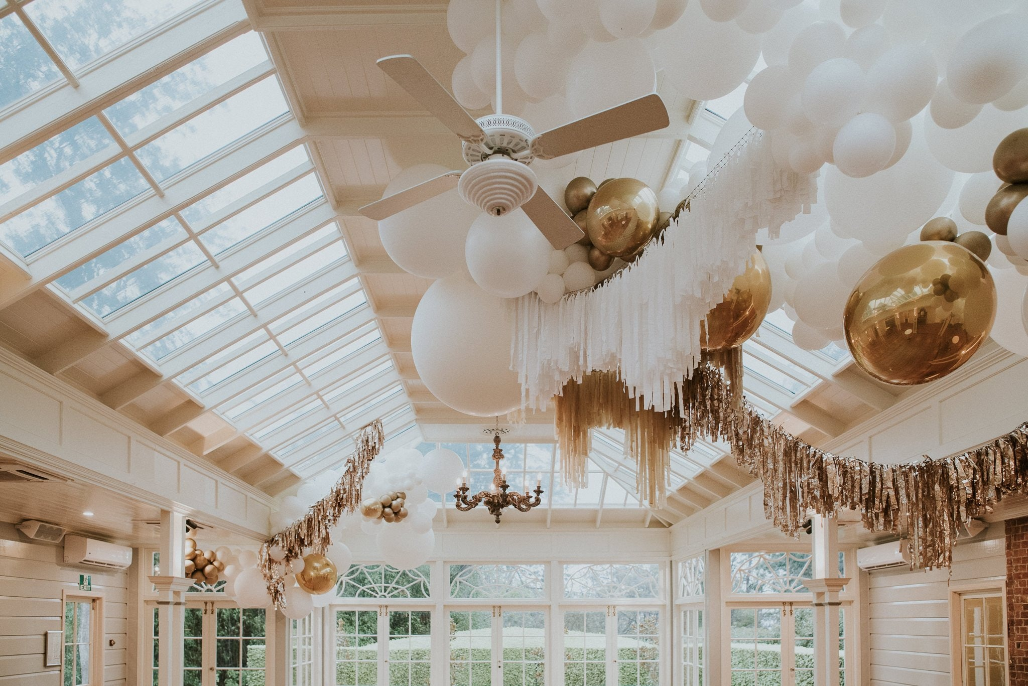 Conservatory with glass ceiling with balloons and garlands hanging from the roof