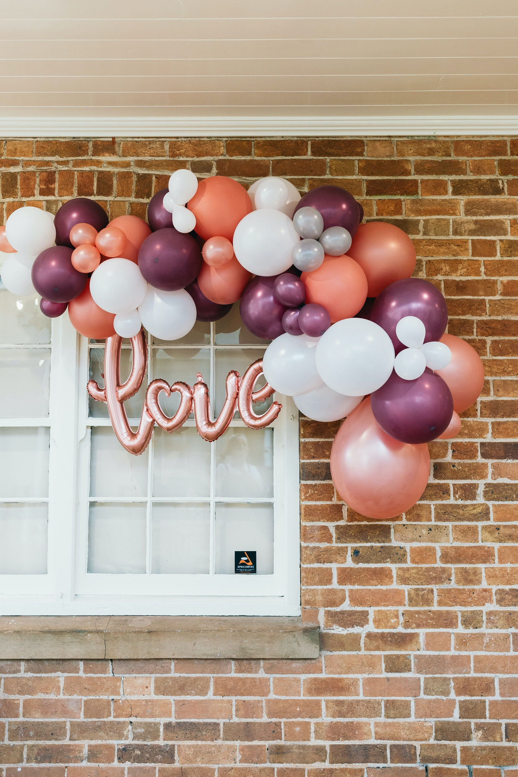 Pink balloon that says 'LOVE' hanging on a brick wall surrounded by pink, purple and grey balloons