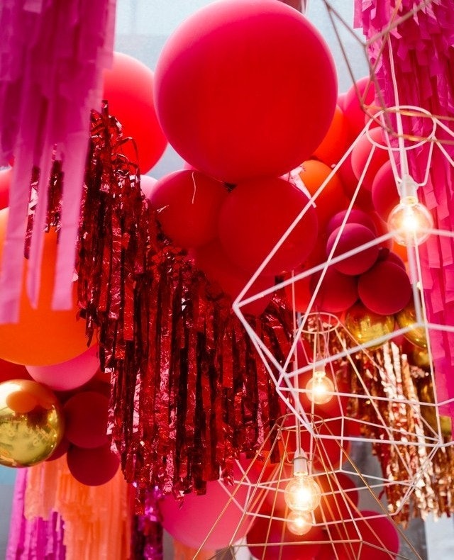 Red, pink and orange balloons and garlands hanging from the roof.