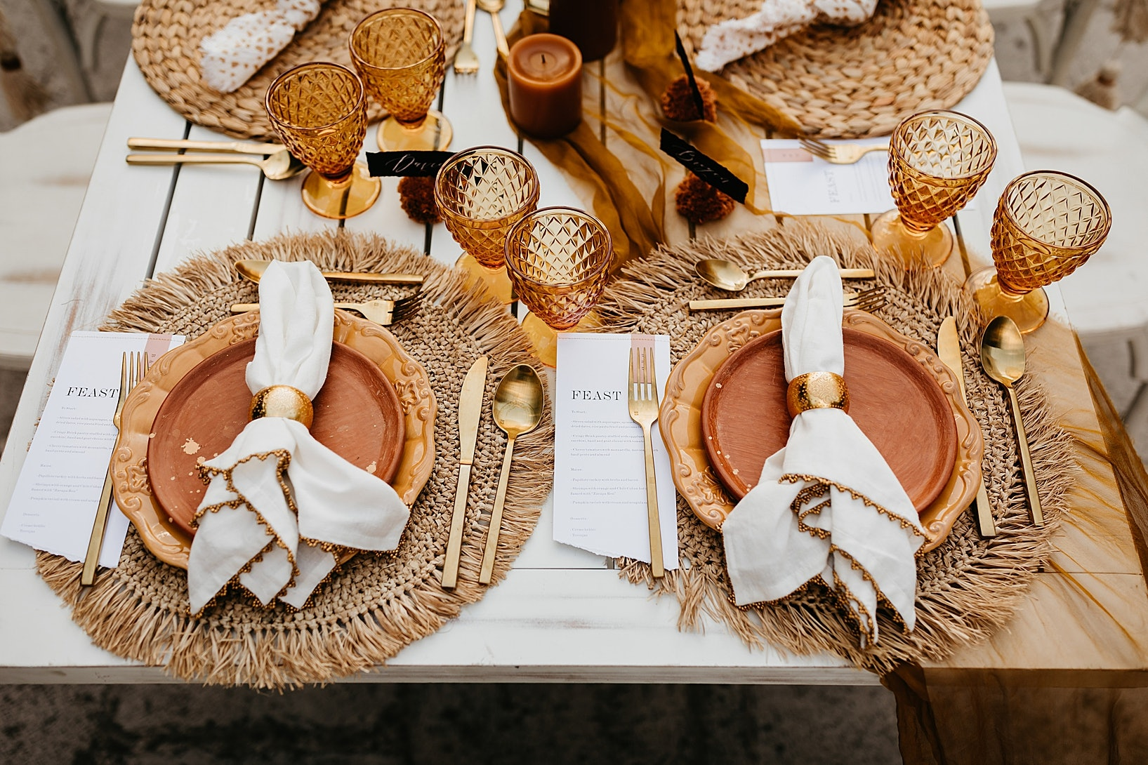 Table set with raffia placemats, mustard coloured plates and amber coloured glasswear