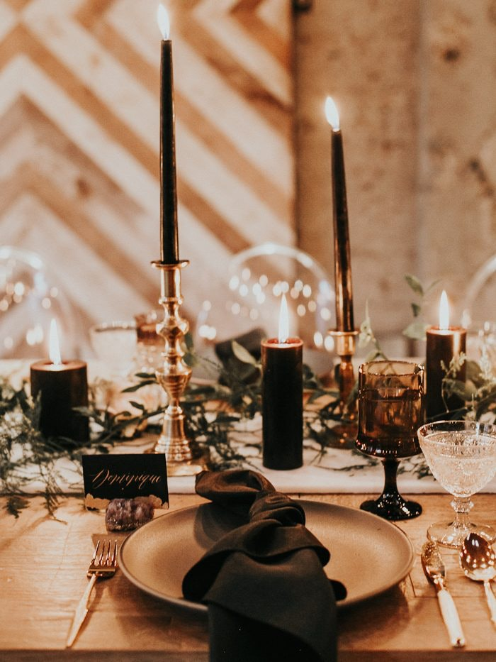 Table set with black tapered candles and pillar candles, black napkins and gold cutlery