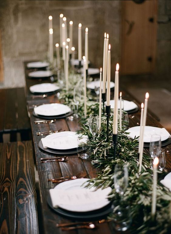 Rustic table set with green olive leaf garlands and white taper candles