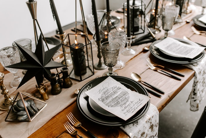 Table set with black plates, gold cutlery, black geometric candles and brass geometric styling shapes