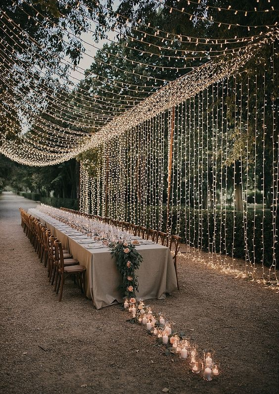 Long outdoor table set for a wedding with fairy lights trellised above