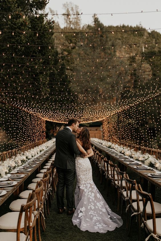 Bride and groom kissing under fairy light outdoor trellis