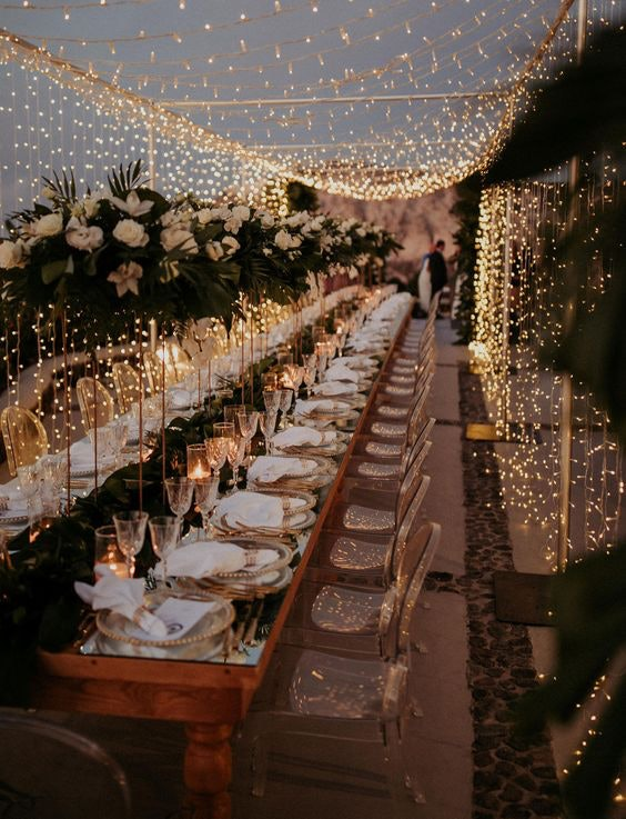 Outdoor wedding reception with tables set under an outdoor fairy light trellis