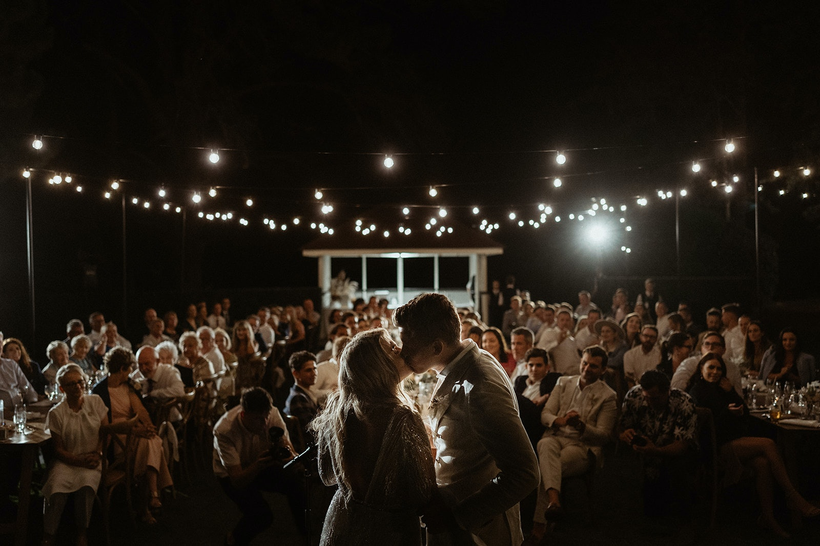bride and groom kissing at night time at their outdoor reception with festoon lights overhead