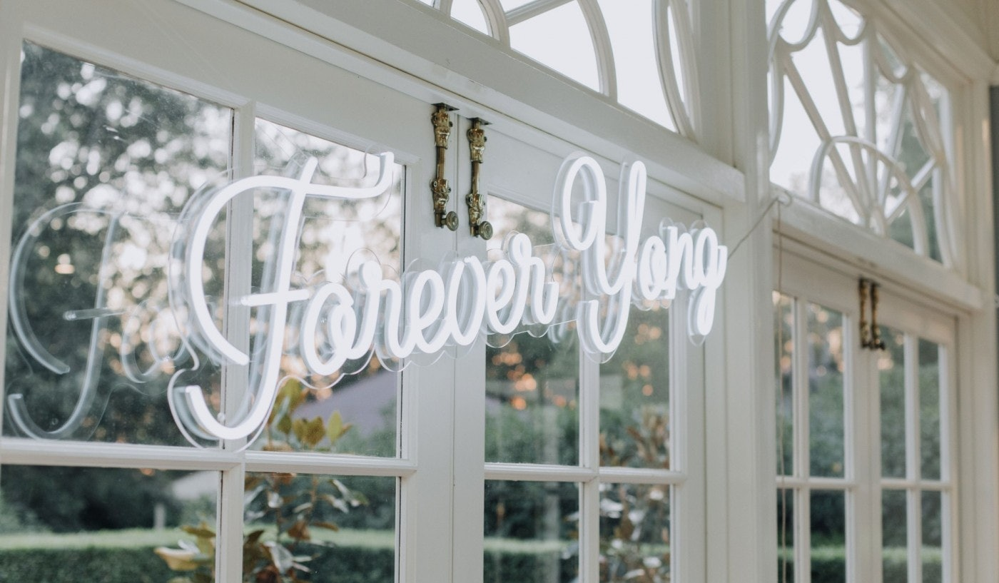 Neon sign hanging on French doors saying 'Forever Yong'