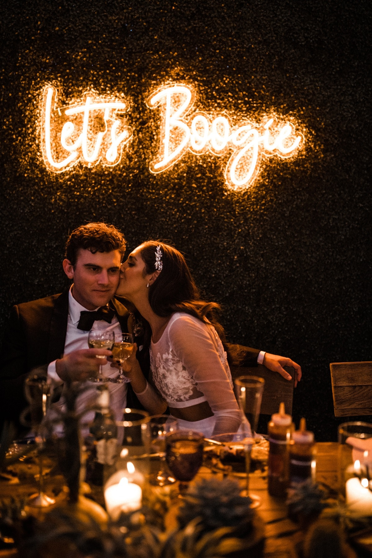 Bride and groom kissing sitting in front of a neon sign saying 'Let's Boogie'