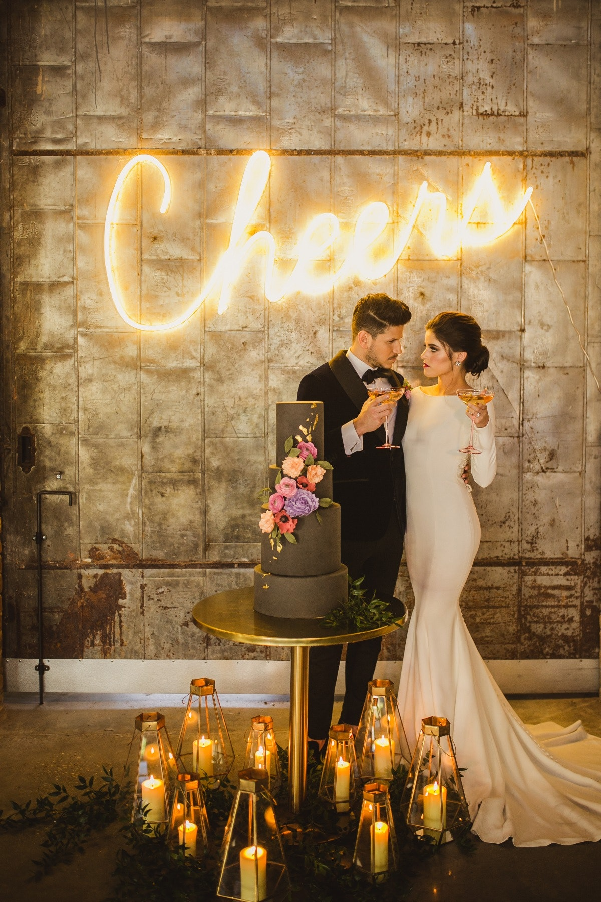 Bride and groom standing behind cake holding champagne under a neon sign saying 'Cheers'