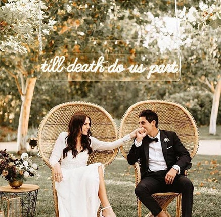 Groom holding bride's hand sitting under a sign saying 'till death do us part'