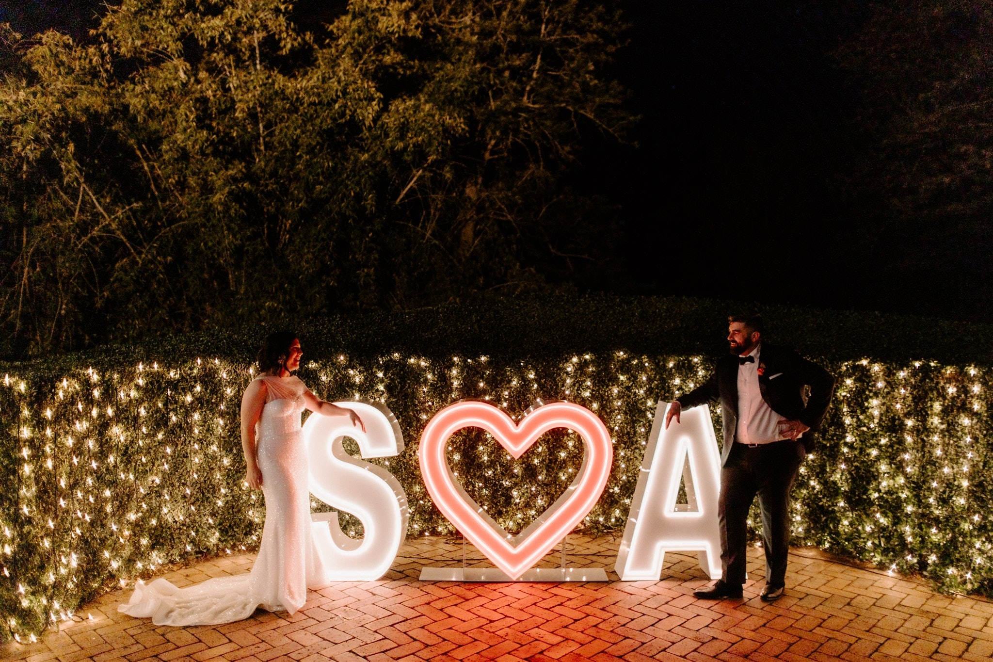 Bride and groom standing either side of light-up letters that say S love heart A