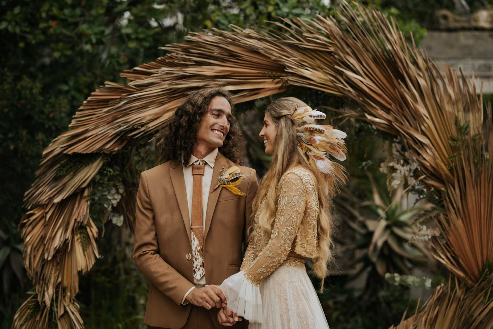 Bride and groom holding hands standing in front of a dried palm frond arbour.