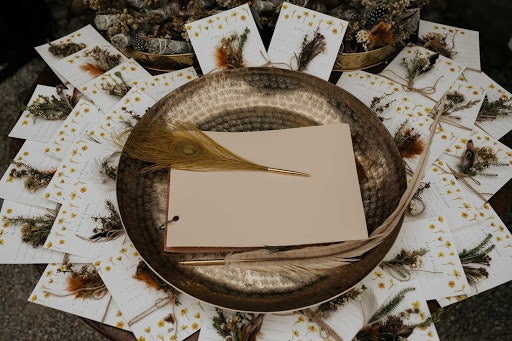 Large gold bowl with writing paper and feather quill for writing inside