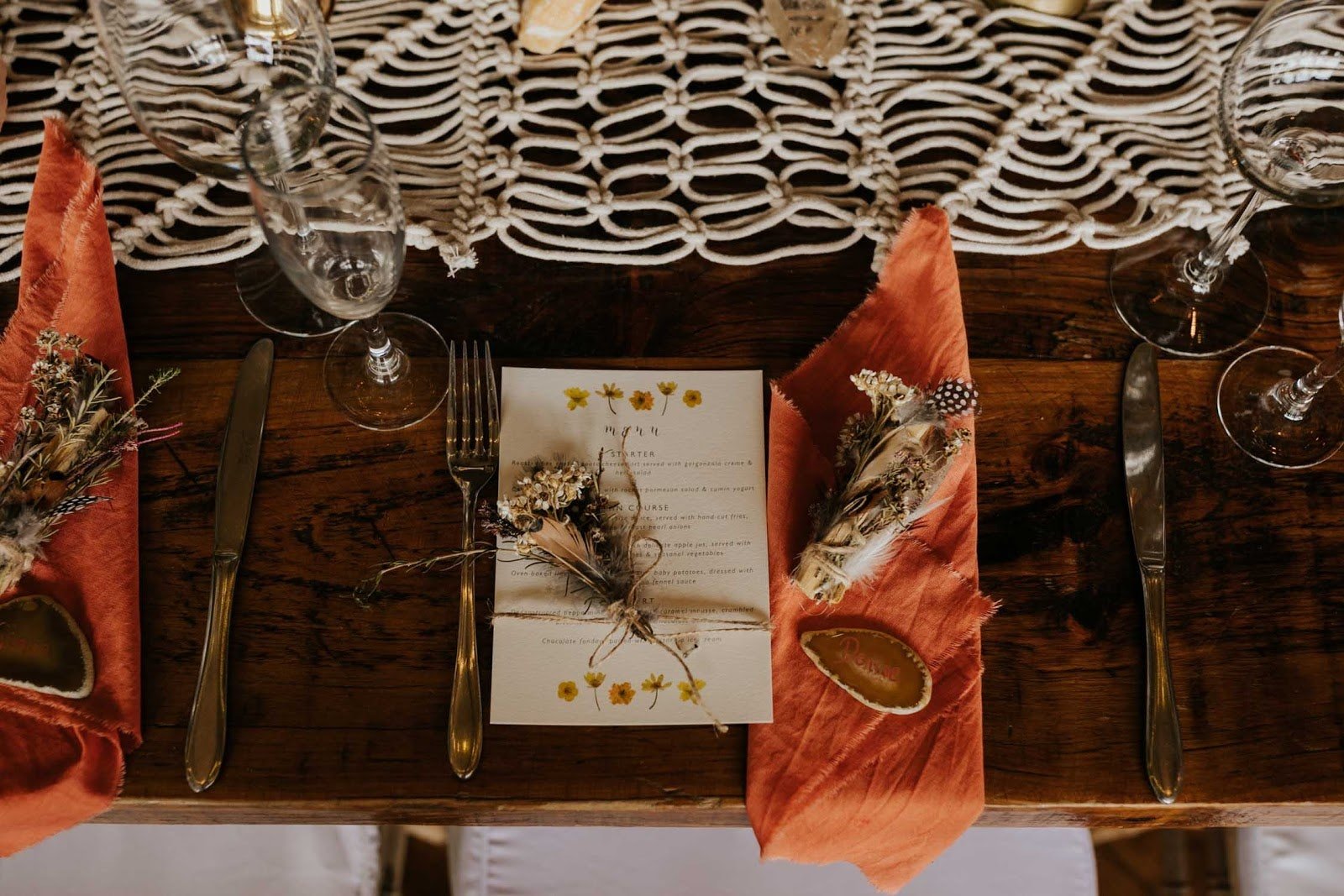 Wedding table setting with orange napkins, macrame table runner and feather styling