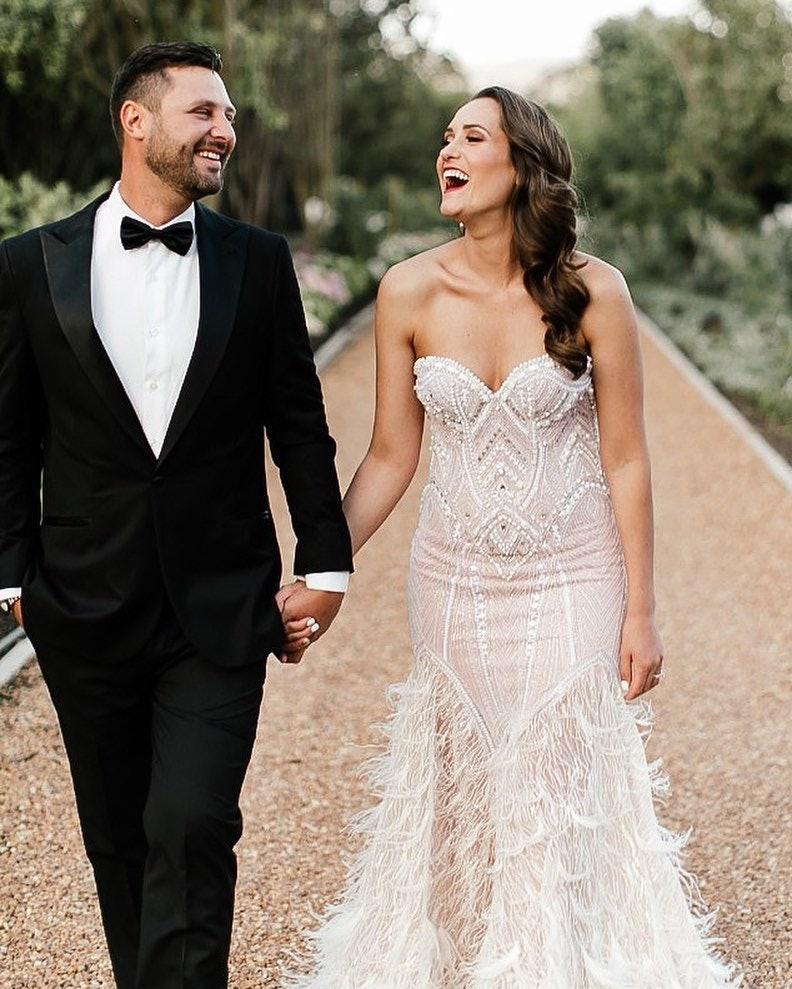 Bride and groom walking along driveway holding hands laughing. Bride has feathers on dress
